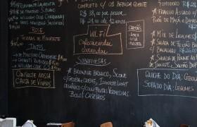 Parede de quadro-negro, com sugestões do dia e outras informações, no Café Carandaí.